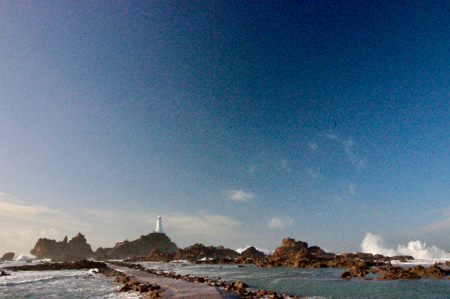 A lighthouse towers over the crashing waves in Jersey