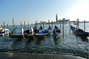 A line of gondolas with the city beyond
